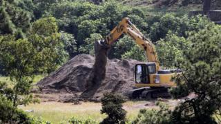 A digger uncovering the mass grave in Jalisco, Mexico, earlier in September