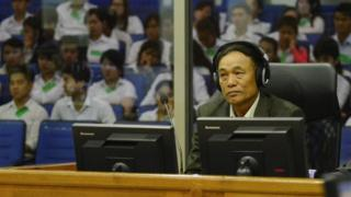 Soy Sen wearing headphones in the trial chamber