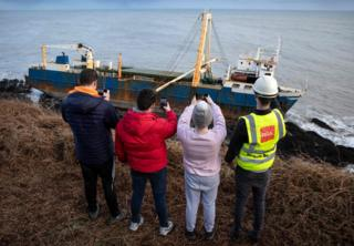 People stand and take photos of the abandoned ghost ship Alta