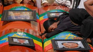 A woman is lying on the coffin during a memorial service for the Ethiopian passengers and the crew who died in the Ethiopian airway accident