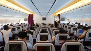 Una cabina de avión con pasajeros a bordo