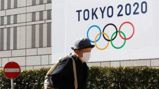 A pedestrian wearing a face mask as a precaution against the Covid-19 coronavirus walks by a signage advertising the Tokyo 2020 Olympic Games in Tokyo.