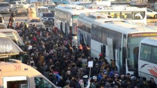 Civilians and rebel fighters are being transported by bus to rebel-held areas west of Aleppo