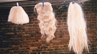 Three wigs on a washing line