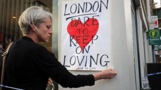 Woman pinning love London poster to post