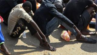 Migrants sit in rows