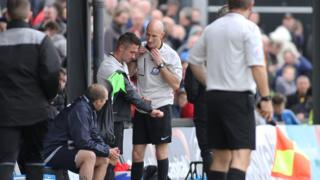 Fourth official Wayne Barratt (R) took over when referee James Adcock retired with an injury