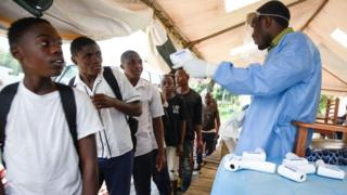 Un agent de santé utilise un thermomètre pour vérifier la température de ressortissants congolais, à la frontière de la RDC avec l'Ouganda, le 12 décembre 2018.