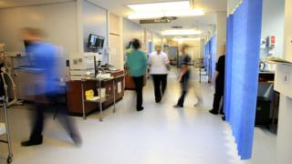 Nurses and other hospital staff walking in a hospital ward
