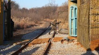 Seorang tentara membuka gerbang di zona demiliterisasi antara Korea Selatan dan Utara (30 November 2018)