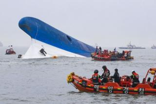 This photo taken at sea some 20 kilometres off the island of Byungpoong in Jindo on 16 April 2014 shows coast guard members searching for passengers near a South Korean ferry (C) that capsized on its way to Jeju island from Incheon