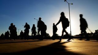 Pessoas caminham em rua movimentada