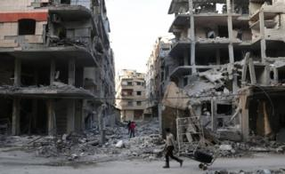 A Syrian youth pulls a cart past destroyed buildings in the town of Ayn Tarma, in the eastern Ghouta