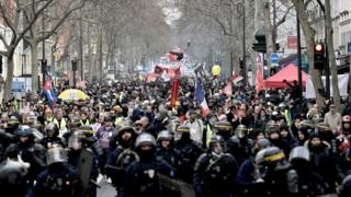 French anti-riot policemen lead the march as protesters demonstrate in Paris, on January 11, 2020