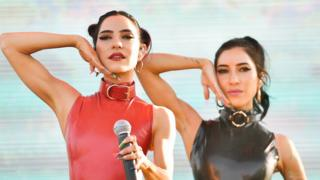 The Veronicas pose with one hand raised next to their cheeks in a performance in Los Angeles in 2019