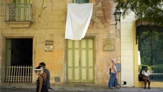 A white bedsheet hangs from a balcony in Old Havana as a tribute to Havana's city historian, Eusebio Leal, on August 1, 2020 in Havana, Cuba.