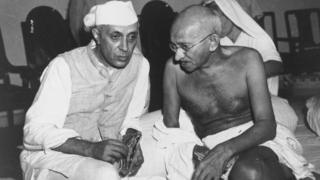 Indian statesmen Mahatma Gandhi (Mohandas Karamchand Gandhi, 1869 - 1948) and Jawaharlal Nehru (1869 - 1964) (left), known as Pandit Nehru, in conversation at the All-India Congress committee meeting at Bombay