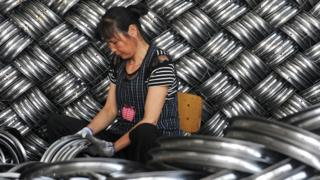 A woman works in a factory making steel hubs in China