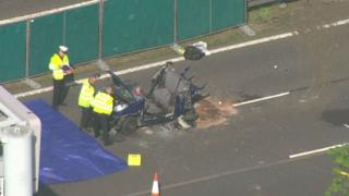 Police stand and observe crushed car
