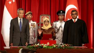 President-elect Halimah Yacob (C) takes the oath of office while flanked by Singapore Prime Minister Lee Hsien Loong (L) and Chief Justice Sundaresh Menon (R) during the presidential inauguration ceremony at the Istana Presidential Palace in Singapore