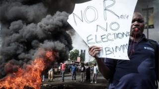 An opposition supporter holds a placard during a protest against Independent Electoral and Boundaries Commission (IEBC) in Kisumu, Kenya, on 11 October 2017