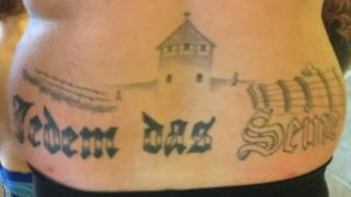 A tattoo, apparently of Auschwitz death camp, for which the wearer is being prosecuted