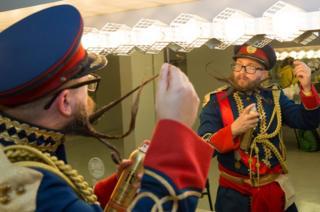 A man sprays his beard.