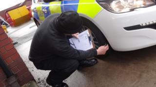 Volunteer checks police car