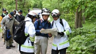 Twelve men, part of a search team looking for the missing boy, in woods, on 30 May 2016.