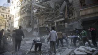 Syrian civilians and rescuers search for survivors following air strikes in the rebel held neighbourhood of Al-Shaar in Aleppo, 27 September 2016