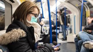 Woman wearing face mask on Tube