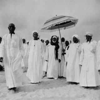 Men dressed in white boubous and turbans walk together. One of them is sheltered from the sun by another man who holds a parasol over his head.
