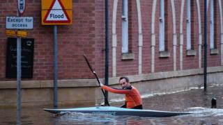 A man paddles his kayak along a flooded street in York, England