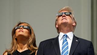 El presidente de Estados Unidos, Donald Trump, y su esposa y primera dama Melania Trump, miran al cielo con las gafas especiales para ver el eclipse el 21 de agosto.
