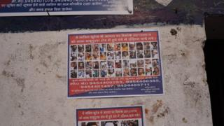 "Posters of ""wanted people"" outside a police station"