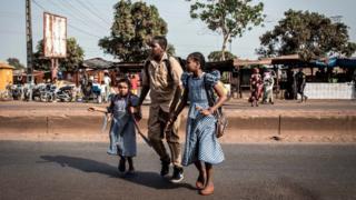 Schoolchildren cross a road in Conakry on Thursday.
