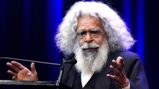 Uncle Jack Charles stands at a lectern