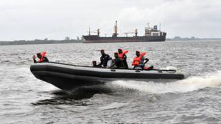 Coast guard officers sit in a speed boat during a patrol, at the port of Abidjan, in 2012