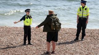 Police instruct walker on beach in Briton, East Sussex