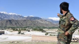 阿富汗一士兵指着山谷中炸弹之母落下的地方