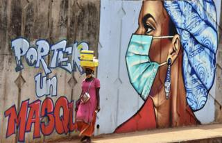 in_pictures A woman walks past graffiti on a wall depicting hygiene measures to curb the spread of Covid-19 in Conakry, Guinea.