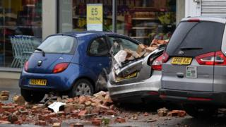 Bricks and debris cover damaged cars after part of a building collapsed in Herne Bay, Kent