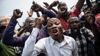 Supporters of the former candidate of the Lamuka opposition coalition, Martin Fayulu, shout in protest after the protest march organized on June 30, 2019, the Independence Day, in Kinshasa was stopped by the police. - Police in the DR Congo capital Kinshasa used teargas on June 30 to break up an opposition march and blocked a car transporting former presidential candidate Martin Fayulu.