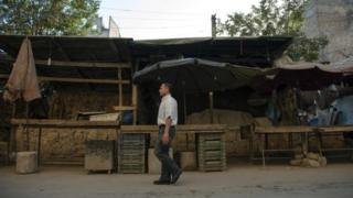 A Syrian man walks in front of an empty vegetable market