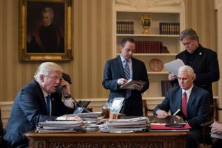 El presidente de EE.UU., Donald Trump, habla por teléfono desde el Despacho Oval de la Casa Blanca con el presidente ruso, Vladimir Putin, rodeado (de izquierda a derecha) del jefe de personal de la Casa Blanca Reince Priebus, el vicepresidente Mike Pence (sentado), y su estratega jefe, Stephen Bannon.