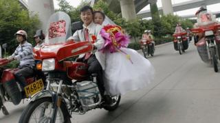 A Chinese bride and groom on a motorcycle
