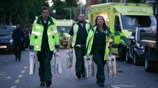 Paramedics carrying oxygen cylinders