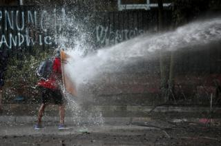 A demonstrator holds a makeshift shield to cover himself from a water cannon aimed by riot police during a protest against Chile's government in Santiago