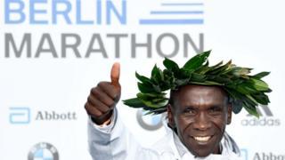 Eliud Kipchoge sur le podium du marathon de Berlin, une couronne de laurier autour de la tête