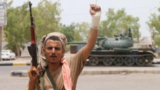 An armed separatist fighter celebrates after seizing a military base during clashes with government forces in Aden on 10 August
